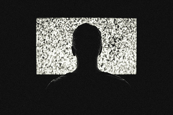 Silhouette of back of person's head looking at TV screen with static